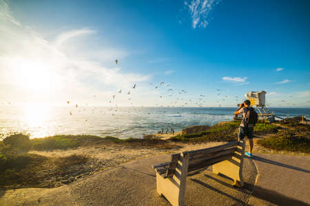 Photographer taking a picture in La Jolla at sunset, California