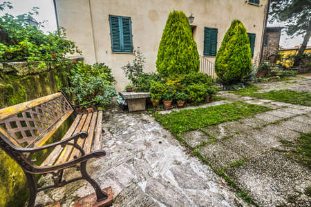 discolored: wooden bench in a picturesque corner in Tuscany, Italy Stock Photo