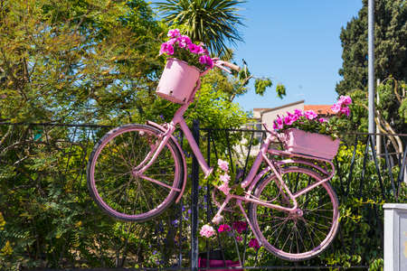 lear: Alghero, Italy - April 29, 2017: Pink bike with flowers hung on a fence