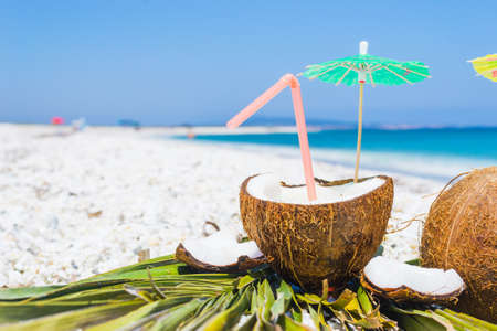 Cocktail umbrellas and straw in a coconut half