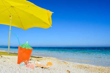 Gele parasol en oranje drankje op het strand