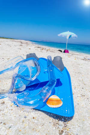 Flippers, snorkel and diving mask on the sand