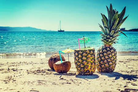 Sluit omhoog van ananassen en kokosnoten door de kust op een duidelijke de zomerdag in uitstekende toon Stockfoto