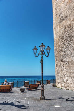 Lamppost by a historic sighting tower in Alghero. Sardinia, Italy