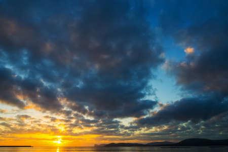 Dark clouds over the sea at sunset. Sardinia, Italy