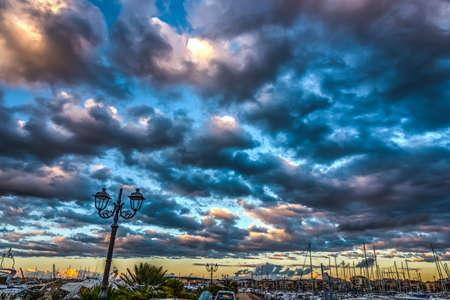 Dramatic sky over Alghero harbor at sunset. Sardinia, Italy