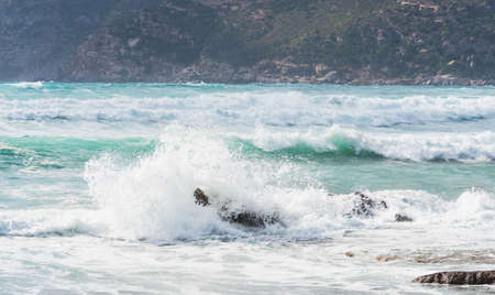 Wave crashing ona rock in Porto Ferro, Sardinia Stock Photo