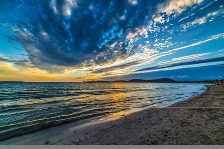 Blue and yellow sky over the sea at sunset. Alghero, Italy