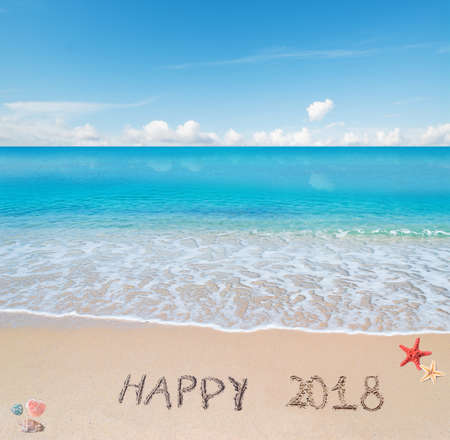 happy 2018 written on a tropical beach