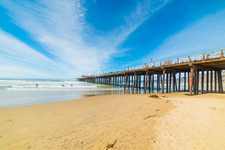 Pismo Beach, CA, USA - October 29, 2016: Surfers by the pier