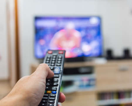 Close up of a man surfing the channels