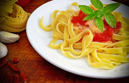 tagliatelle, tomato and basil plate surrounded by raw ingredients