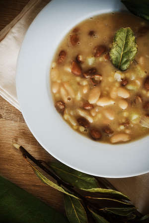 White plate with fregola and beans soup on a wooden table