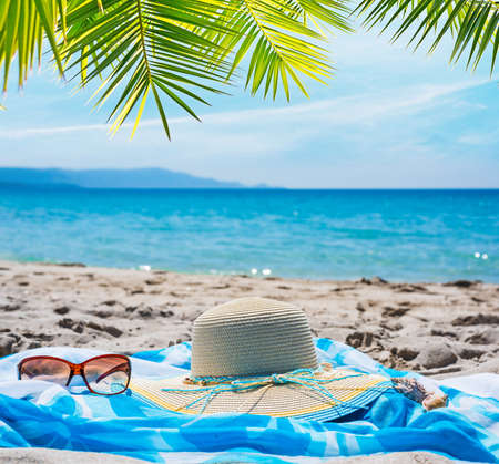 Straw hat and sunglasses on the sand by the sea under a palm tree