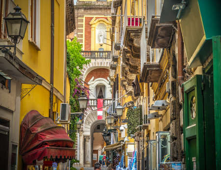 Narrow alley with Duomo steeple on the background in world famous Sorrento. Campania, Italy