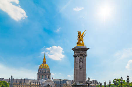 Pegasus golden statue on Alexander III bridge and Army museum on the background under a shining sun. Paris, France