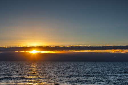 Sun shining through dark clouds over the sea at sunset. Sardinia, Italy