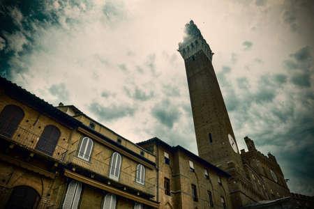 Sun shining over Torre del Mangia in Piazza del Campo. Siena, Italy
