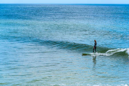 Surfer surfing a small wave on a longboard in Florida, USA