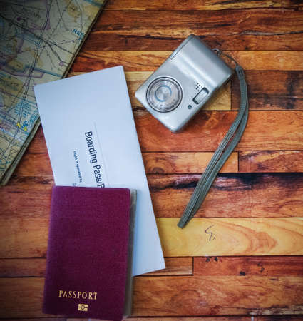 Passport, boarding pass, camera, map on a wooden table