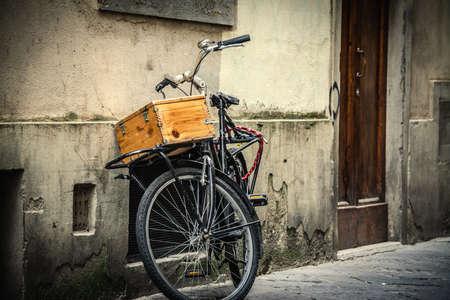 Bicicleta vieja con caja de madera apoyada contra una pared en Florencia, Italia.