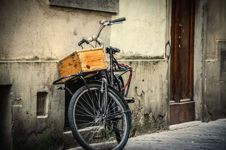 Old bike with wooden case leaning against a wall in Florence, Italy