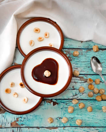 Flat lay of Italian dessert panna cotta with hazelnuts and caramel Standard-Bild - 134866057