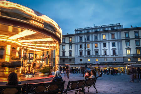 People by a vintage carousel in Florence at night. Tuscany, Italy