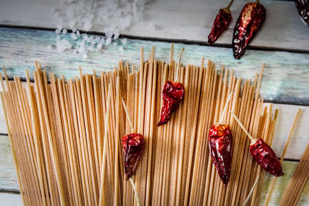 Wholegrain spaghetti and chili peppers on a wooden table seen from above 스톡 콘텐츠 - 138429859