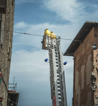Two firemen on a ladder surrounded by bees in Italy Stock Photo