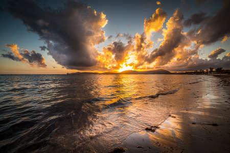 Dark clouds and shining sun over Alghero shore at sunset. Sardinia, Italy Reklamní fotografie