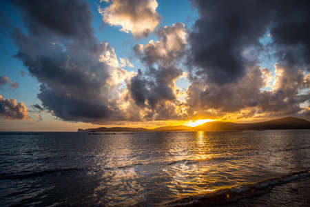Dark clouds over the sea in Alghero at sunset. Sardinia, Italy