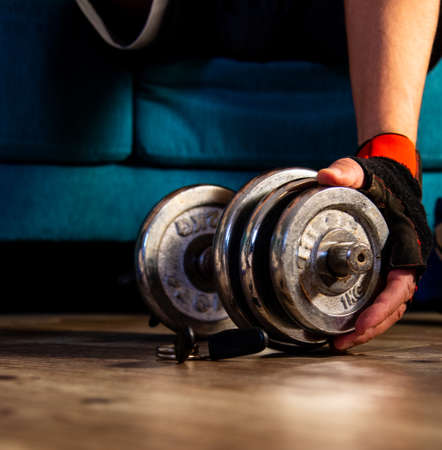 Close up of a man holding a metal dumbbell during a home workout