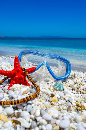 Diving mask, starfish ans necklace on pebbles in sumer