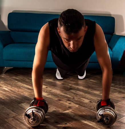 Front view of a man doing plank with dumbbells in the living room during home workout