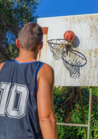 Basketball player on a backyard basketball court in summer