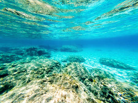 Underwater view of rocks and sand in Alghero sea bed. Sardinia, Italy