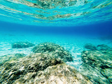 Underwater view of Alghero shore with rocks and white sand. Sardinia, Italy