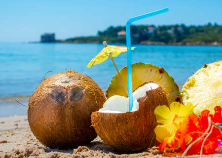 Close up of a drink made with coconut surrounded by pineapple and summer objects on the beach on a sunny day