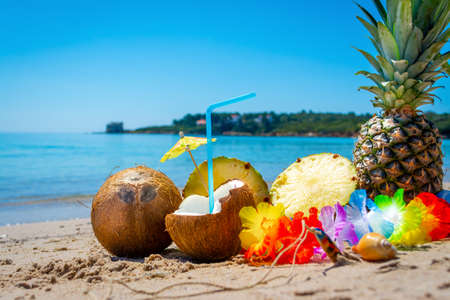 Drink made with coconut surrounded by pineapple and summer objects on the beach on a sunny day Zdjęcie Seryjne