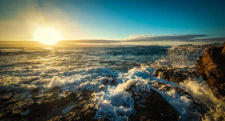 Sun shining over Alghero rocky shore at sunset. Sardinia, Italy