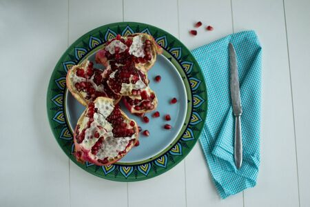 Large ripe pomegranate and scattered grains on a turquoise plate with a metal knife on a plaid napkin