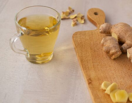 Fresh ginger tea on a light background. Ginger is suitable for cooking and preparing drinks. Фото со стока