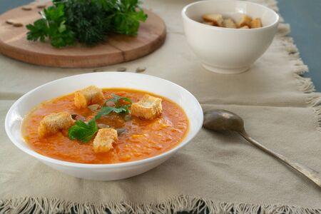 カボチャとニンジンスープ、種、クラッカー、パセリ。ベジタリアンスープ。 写真素材