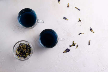 Anchan Thai blue tea in two glass cups and a bowl with dry flowers. Beautiful indigo color. Copy space. Top view.