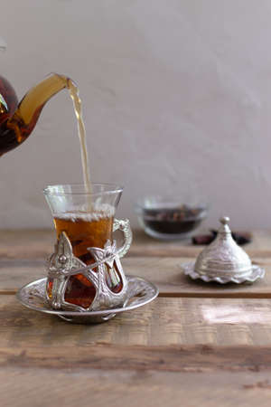 Turkish tea in a traditional glass cup on a wooden table. Tea pouring process. Copy space. Vertical orientation. 免版税图像