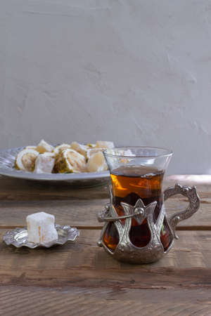 Turkish tea in a traditional glass cup on a wooden table. Eastern sweets and a hot drink. Copy space.