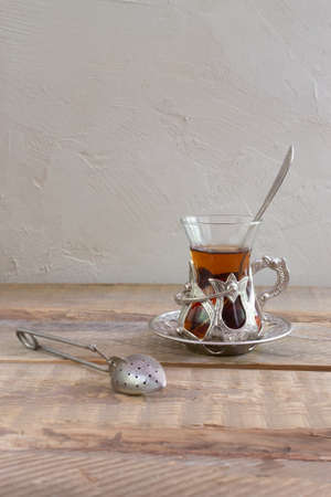 Delicious Turkish tea with a traditional glass cup with a metal teapot on a wooden table. Copy space. Vertical orientation.