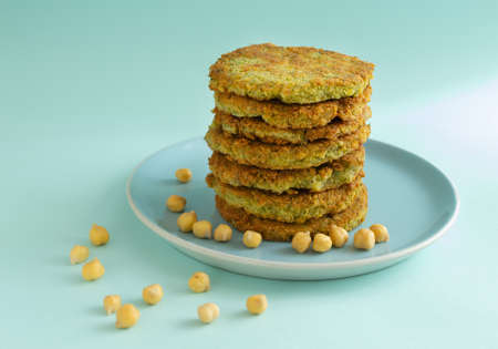 A stack of veggie burgers with chickpeas and vegetables on a blue background. Vegetarian food concept. Copy space.