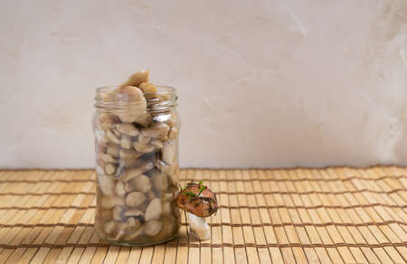 Pickled forest mushrooms in a glass jar on a wooden background. Autumn gifts. Horizontal orientation. Copy space.